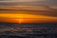 Bright orange sunset on the Atlantic off the Florida coast. Blue water with broken clouds Royalty Free Stock Photo