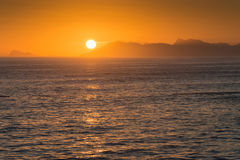 Orange sunset in Dekelders, South Africa. A bright orange sunset over the mountains, Dekelders, near Gansbaai, South Africa royalty free stock photos
