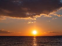 Bright orange sunset over the sea - islands on the horizon royalty free stock images