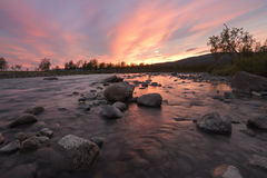 Bright orange sunset over wild river with big rocks and orange reflection. Waiting for the sunset giving this beautiful orange glow over this river, Sarek royalty free stock photo
