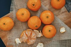 Bright orange tangerines clementines on a wooden background wi. Bright orange tangerines clementines whole and peeled with rind on a wooden background with stock images