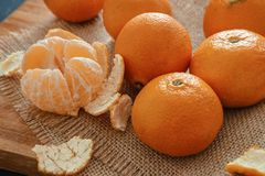 Bright orange tangerines clementines on a wooden background wi. Bright orange tangerines clementines whole and peeled with rind on a wooden background with stock photos