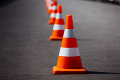 Bright orange traffic cones. Standing in a row on dark asphalt Stock Images