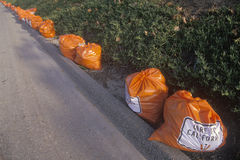 Bright orange trash bags along a roadway waiting for pickup Royalty Free Stock Images