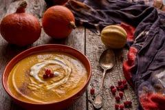 Bright orange useful pumpkin soup. Bright orange useful pumpkin soup soup on an old wooden cracked background. Dark photo vintage style. Useful homemade simple Stock Image