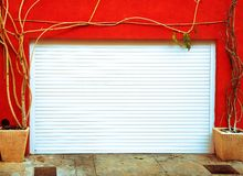 Bright orange wall with a white garage door Royalty Free Stock Photos