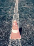 Bright orange white plastic cone on painted white line. Very dry  football playground Stock Images