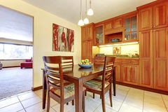 Bright orange wood kitchen and dining room with tile floor. Royalty Free Stock Photos