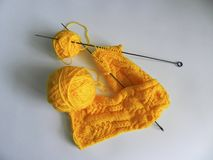 Bright orange-yellow yarn with knitting needles. Macro. royalty free stock photography