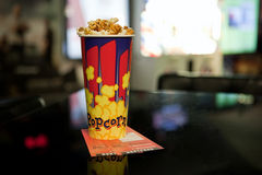Bright paper cup of popcorn and two movie tickets. On a black table with a blurred background Stock Images