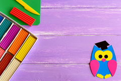 Bright paper owl, colorful plasticine set, plastic board and knife on wooden background with blank space for text. Children education. Back to school background royalty free illustration