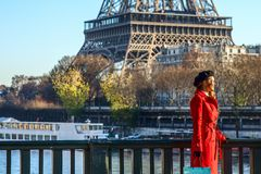 Woman standing on embankment near Eiffel tower in Paris, France Stock Images
