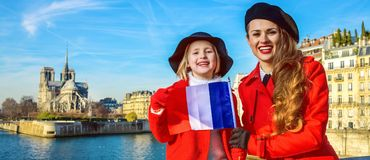 Portrait of mother and child tourists in Paris with French flag. Bright in Paris. Portrait of modern mother and child tourists in red coats on embankment in Stock Photos