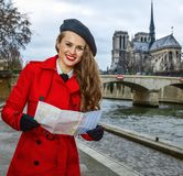 Smiling traveller woman on embankment in Paris, France with map Stock Photos