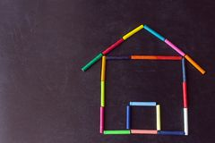 Bright pastel crayons are arranged in the shape of a house on a. Black school slate. Children`s creativity. Concept- sweet home, back to school, mortgage, your royalty free stock photos