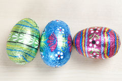 Bright patterned easter eggs. Three patterned easter eggs on a wood grain background Royalty Free Stock Image