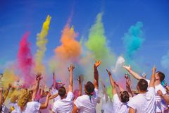 Bright People celebrate the holiday Holi, a group of people throw paint in the blue sky royalty free stock image