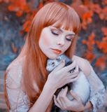 Bright photo, red-haired girl with straight hair and bangs holds cute sleeping ferret in her hands, lady with closed royalty free stock photo