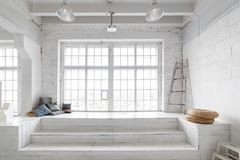 Bright photo studio interior with big window, high ceiling, white wooden floor.  stock photo