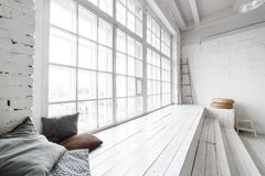 Bright photo studio interior with big window, high ceiling, white wooden floor.  Royalty Free Stock Images