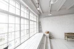 Bright photo studio interior with big window, high ceiling, white wooden floor Stock Images