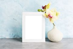 Bright photoframe mockup with yellow orchid against light blue wall. Interior design concept. Text space Royalty Free Stock Photos