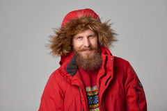 Bright picture of handsome man in winter jacket. Closeup portrait of bearded man in red winter jacket with hood on, over grey background Stock Photos