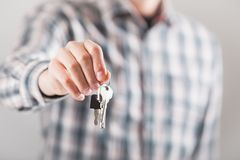 House key in hand. Bright picture of man hand holding house keys Royalty Free Stock Images