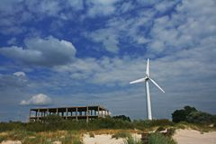 Bright picture of wind turbine standing near unfinished building. Bright picture of wind turbine standing in the sand near unfinished building Royalty Free Stock Images