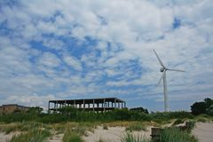 Bright picture of wind turbine standing in the sand near unfinished building. Cloudy day Stock Photo