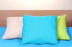 Bright pillows on bed Stock Images