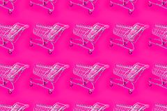 Bright pink background with a trolley for the supermarket. stock photography