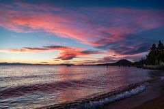 Pink and blue sunset with gentle waves in lower right corner from Lakeside Beach at Lake Tahoe. Bright pink and blue sunset with gentle waves in lower right royalty free stock images