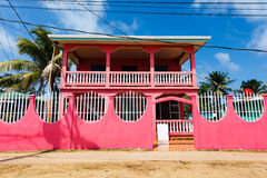 Bright pink facade of 2 story house on a dirt road Royalty Free Stock Photography