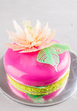 Bright pink mousse cake with mirror glaze. Mousse cake with pink mirror glaze on lime green biscuit with tempered chocolate flower decoration. Modern european stock photography