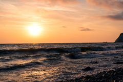Bright pink-orange dawn over water storm wind with waves.  royalty free stock photo
