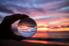 Bright Colorful Sunset over Ocean Captured in Glass Ball. Bright pink orange and purple sunset clouds reflecting on ocean surface captured in glass ball royalty free stock photography
