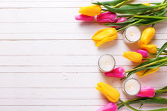 Bright pink and yellow tulips  flowers and candles  on white woo. Den background. Selective focus. Top view. Flat lay. Place for text Stock Photography