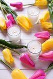 Bright pink and yellow tulips  flowers and candles. On white wooden background. Selective focus. Top view Royalty Free Stock Photography