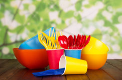 Bright plastic bowls, forks, spoons and cups on abstract green. Stock Photos