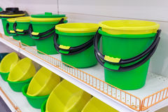 Bright plastic buckets and bowls on the counter. Sale royalty free stock photo