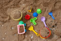 Bright plastic children`s toys in the sand. Concept of beach recreation for children. stock photography