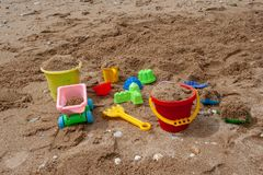 Bright plastic children`s toys in the sand. Concept of beach recreation for children. royalty free stock images