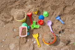 Bright plastic children`s toys in the sand. Concept of beach recreation for children. stock images