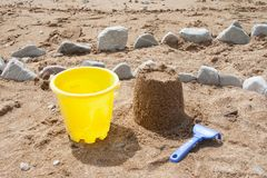Bright plastic children`s toys in the sand. Concept of beach recreation for children. royalty free stock image