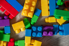 Bright plastic construction blocks on background grey wooden . Developing toys. Early learning. Frame. Top view. Stock Image