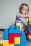 Bright plastic construction blocks with unrecognizable child girl on background. Developing toys. Early learning. Stock Images