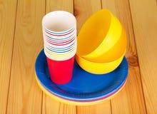 Bright plastic tableware on  background of light wood. Stock Image