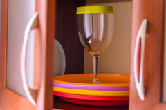 Bright plastic tableware in cupboard royalty free stock photo