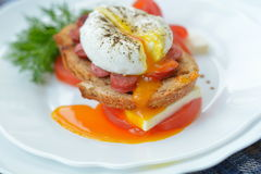 Bright poached egg and sandwich - breakfast in restaurant. Bright yolk of spiced poached egg, sandwich with cheese, sausage, tomato and herbs on white plate Royalty Free Stock Photography